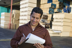 Supervisor Stock Taking In Warehouse. Male supervisor stock taking outside warehouse against stack of wood Stock Image