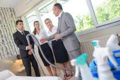 Supervisor with team cleaners in hotel room Stock Image