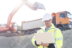 Supervisor using laptop at construction site on sunny day Royalty Free Stock Photos