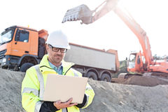 Supervisor using laptop at construction site on sunny day Stock Photo