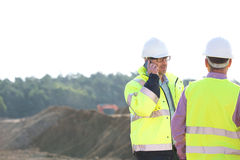 Supervisor using mobile phone while standing with colleague at construction site against clear sky Stock Image