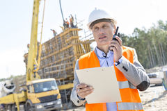 Supervisor using walkie-talkie while holding clipboard at construction site Stock Image