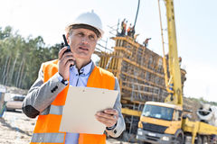 Supervisor using walkie-talkie while holding clipboard at construction site Royalty Free Stock Image