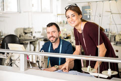 Supervisor and worker in a factory. Portrait of a good looking female supervisor and a male tailor working together in a textile factory Stock Photography