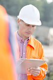 Supervisor writing on clipboard at construction site Stock Image