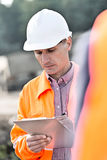 Supervisor writing on clipboard at construction site Stock Photos