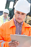 Supervisor writing on clipboard at construction site with colleague in background Royalty Free Stock Photography