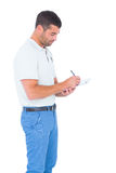 Supervisor writing on clipboard over white background. Side view of male supervisor writing on clipboard over white background Stock Image