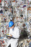 Supervisor Writing On Clipboard In Recycling Factory. Young male supervisor writing on clipboard by stacks of paperwaste in recycling factory Royalty Free Stock Photo