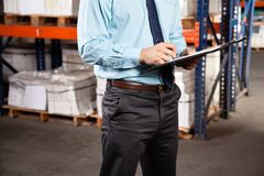 Supervisor Writing On Clipboard At Warehouse. Midsection of male supervisor writing on clipboard at warehouse Stock Photography