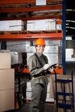 Supervisor Writing On Clipboard At Warehouse. Portrait of young male supervisor writing on clipboard at warehouse Royalty Free Stock Images