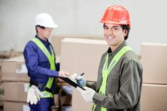 Supervisor Writing Notes Clipboard While Foreman. Portrait of young supervisor writing notes clipboard while foreman working at warehouse Royalty Free Stock Photos