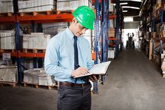 Supervisor Writing Notes At Warehouse. Young male supervisor writing notes at warehouse Stock Images