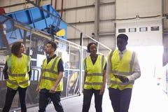 Supervisor y compañeros de trabajo que caminan en un interior industrial imagen de archivo libre de regalías