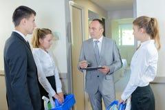 Supervisore che controlla le mansioni del gruppo della lista di controllo di pulizia Fotografia Stock Libera da Diritti