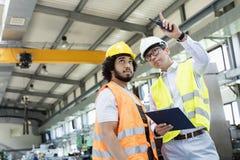 Supervisore che mostra qualcosa al lavoratore manuale nell'industria metalmeccanica immagine stock