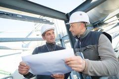 Supervisore con i lavoratori che esaminano i modelli alla tavola nell'industria immagini stock