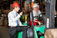 Supervisore con la lavagna per appunti che istruisce carrello elevatore Immagini Stock Libere da Diritti