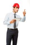 Supervisore della costruzione con la compressa digitale che mostra un progetto Immagine Stock