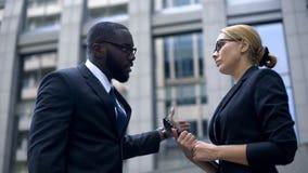 Supervisore insoddisfatto che rimprovera collega, sessismo, diritti delle donne immagini stock
