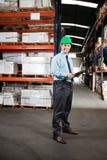Supervisore sicuro con la lavagna per appunti al magazzino Immagini Stock Libere da Diritti