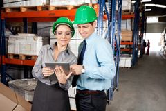 Supervisores que usam a tabuleta de Digitas no armazém imagens de stock