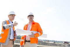 Supervisors with blueprints discussing at construction site against clear sky Stock Image