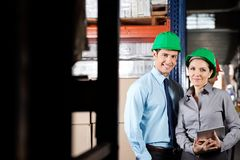 Supervisors With Digital Tablet At Warehouse. Portrait of two young supervisors with digital tablet smiling together at warehouse Stock Images
