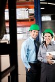 Supervisors With Digital Tablet At Warehouse. Portrait of two young supervisors with digital tablet smiling together at warehouse Royalty Free Stock Photo