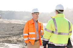 Supervisors discussing at construction site on sunny day Royalty Free Stock Images