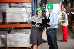 Supervisors And Foreman Working At Warehouse. Supervisors working with foreman unloading cardboard boxes at warehouse Royalty Free Stock Photography