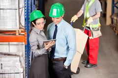 Supervisors And Foreman Working At Warehouse. Supervisors using digital tablet with foreman working at warehouse Stock Photography