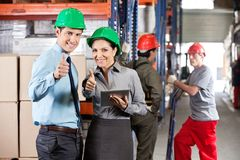 Supervisors Gesturing Thumbs Up At Warehouse. Portrait of supervisors with digital tablet gesturing thumbs up with workers in background Stock Photography
