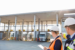 Supervisors looking at truck entering in shipping yard Royalty Free Stock Image
