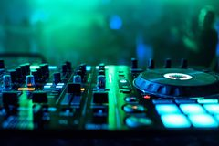 Supervisors and regulators music mixer DJ to play music. With blurred green background Royalty Free Stock Images