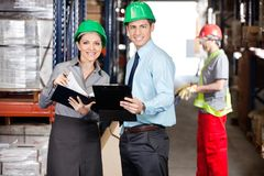 Supervisors Working At Warehouse. Portrait of supervisors with clipboard and foreman unloading cardboard boxes at warehouse Stock Photography