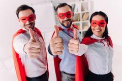Superwirtschaftler in den Masken und Kape, die sich Daumen zeigen lizenzfreie abbildung