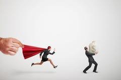 Superwoman die de dief met grote zak geld achtervolgen Stock Foto's