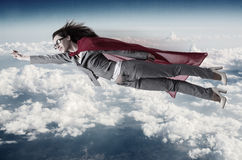 The superwoman flying above the skies Stock Photography