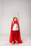 Superwoman kid in red cape raised her hands up Royalty Free Stock Images