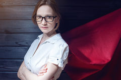 Superwoman office worker standing in a suit and red cloak Stock Photo