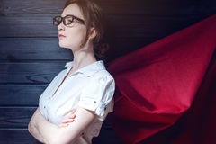 Superwoman office worker standing in a suit and red cloak Stock Photos