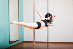 Superwoman pole fitness pose. Gorgeous young woman practicing the superwoman pose during her pole fitness class Royalty Free Stock Images
