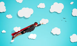 Superwoman in red mask and cloak. Flying through paper clouds over blue background Royalty Free Stock Image