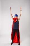 Superwoman in superhero costume raised hands up. Superwoman in superhero costume raised her hands up. Young woman posing in studio stock photo