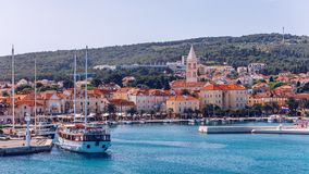 Supetar city in Brac island, Croatia. View from the sea. Picturesque scenic view on Supetar on Brac island, Croatia. Panoramic. View on harbor of town Supetar royalty free stock photo