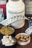 Suplementos nutritivos nas cápsulas e nas tabuletas, no fundo de madeira Foto de Stock Royalty Free