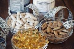Suplementos nutritivos nas cápsulas e nas tabuletas, no fundo de madeira Fotografia de Stock Royalty Free