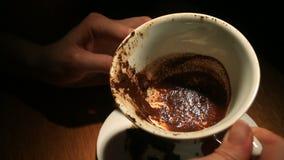 Supondo nas terras de café, uma mão fêmea que guarda uma caneca de café com terras de café Close-up filme