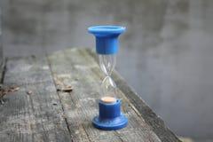 Suporte azul da ampulheta velha na tabela fotografia de stock